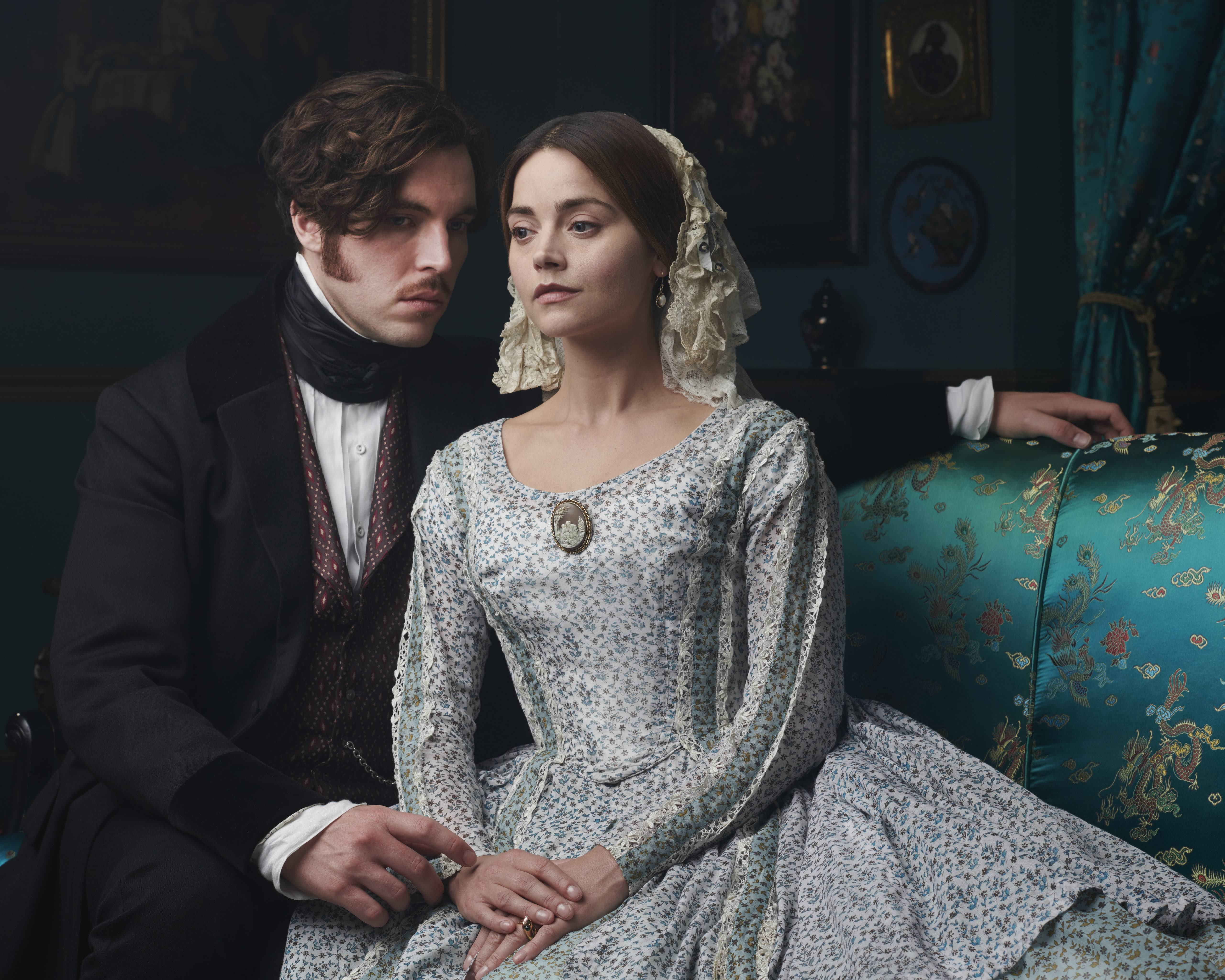 Tom Hughes as Prince Albert and Jenna Coleman as Queen Victoria sitting on a couch