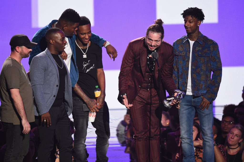 Post Malone, recipient of the award for Song of the Year, and 21 Savage speak onstage during the 2018 MTV Video Music Awards at Radio City Music Hall on August 20, 2018 in New York City.