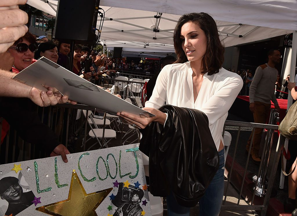 NCIS: Los Angeles actress Daniela Ruah signs autographs.