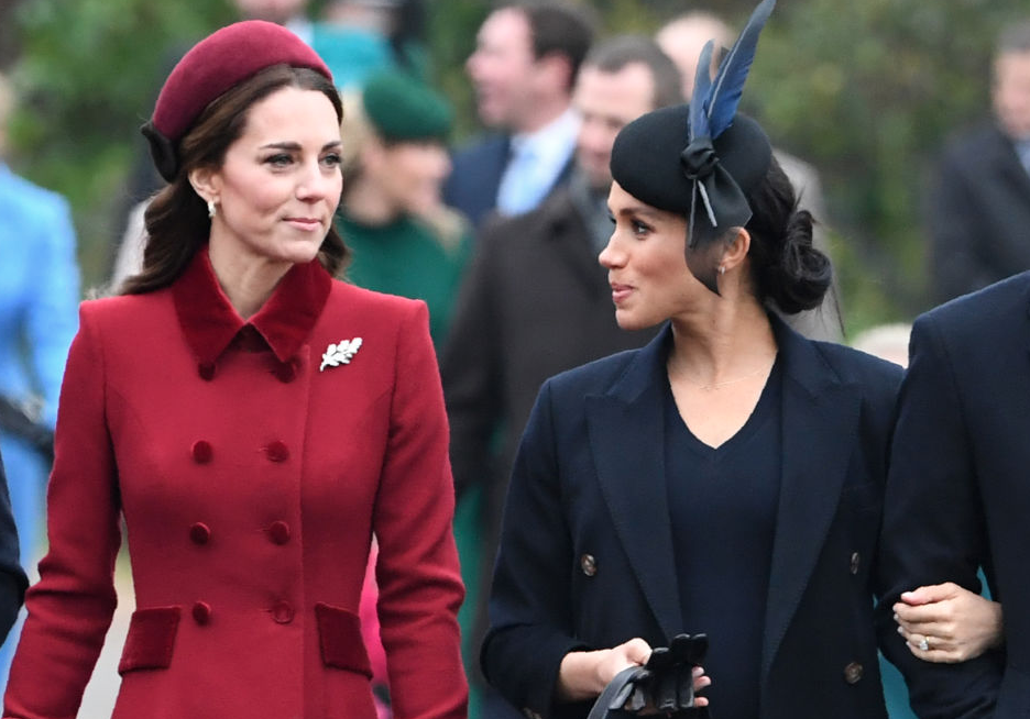 Kate Middleton and Meghan Markle talking to each other.