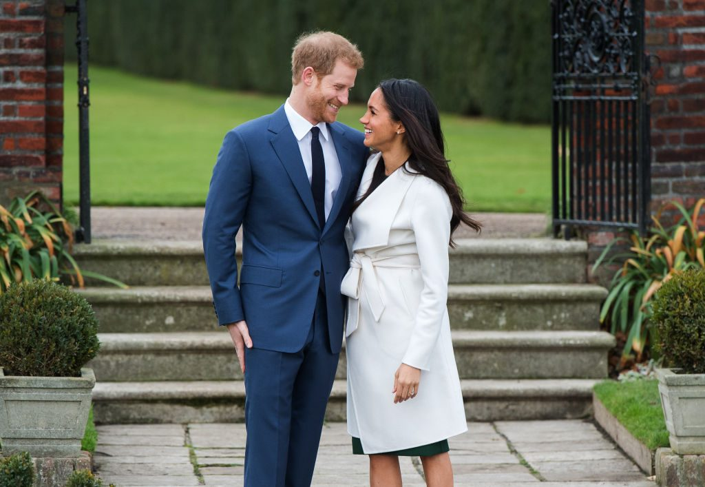 Prince Harry and Meghan Markle smiling at each other outside of Nottingham Cottage.