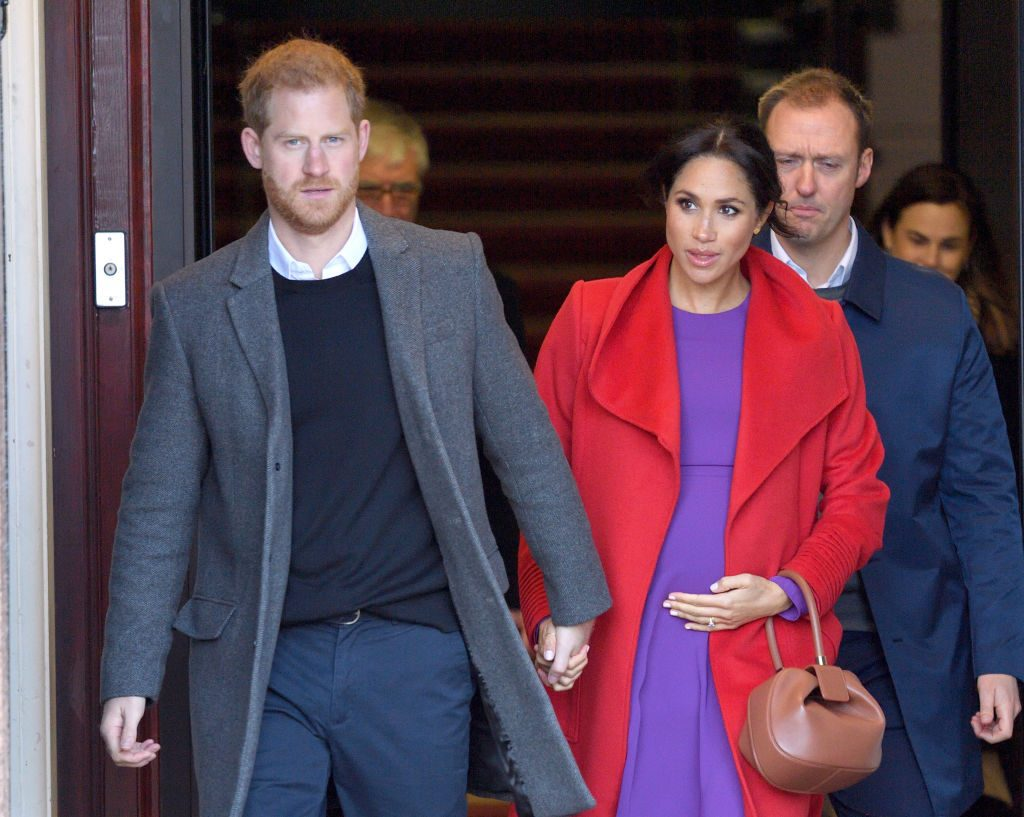 Prince Harry and Meghan Markle hold hands at an event.