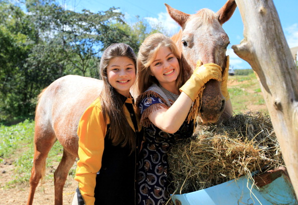 Tori (left) and Erin Bates tend to the horses