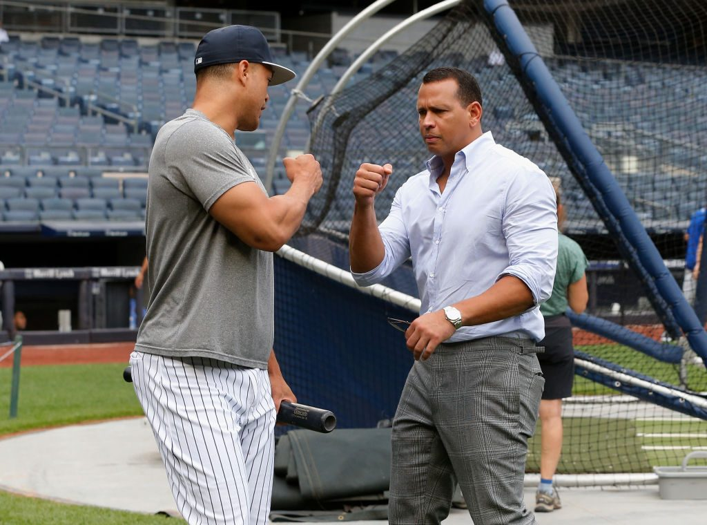 Giancarlo Stanton #27 of the New York Yankees talks with Alex Rodriguez |  Jim McIsaac/Getty Images