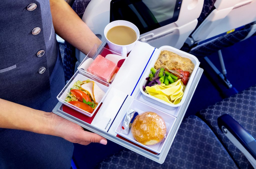 A flight attendant serves a meal