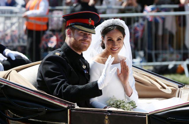 Prince Harry and Meghan Markle on wedding day during carriage ride.