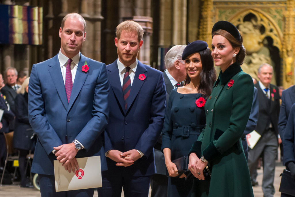 The queen walks in front of the royal family