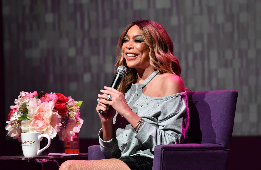 Wendy Williams is smiling holding a microphone