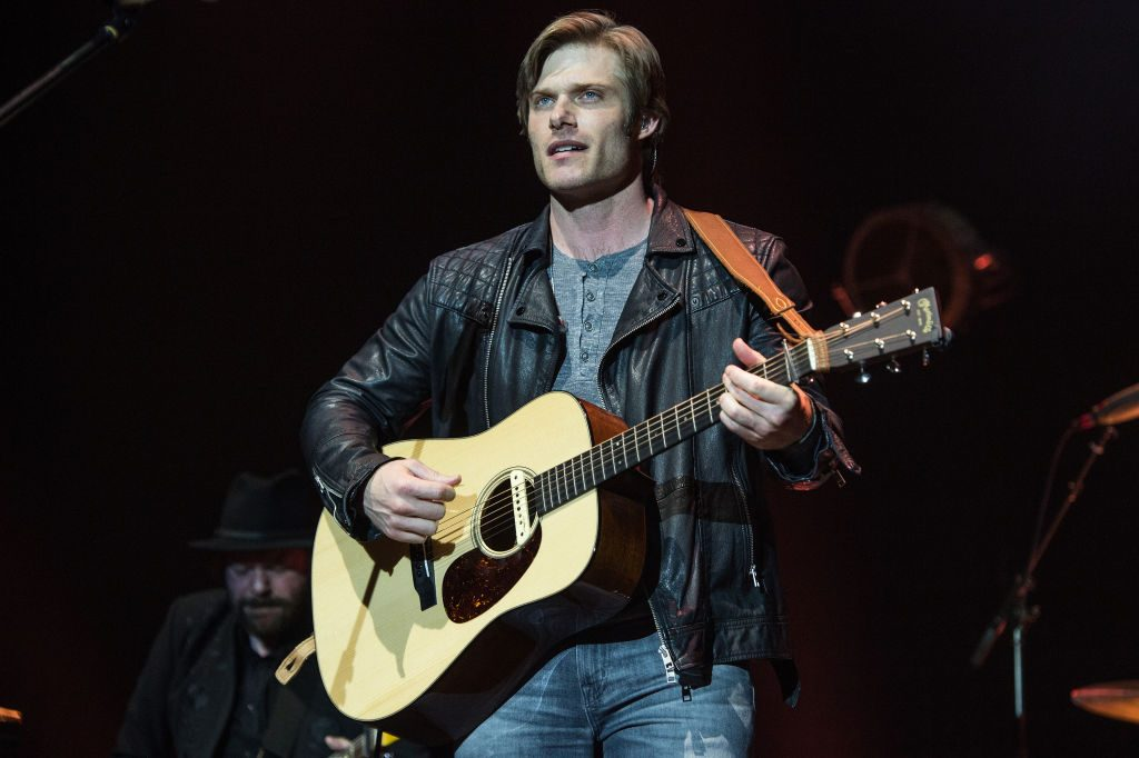 Chris Carmack on stage with a guitar
