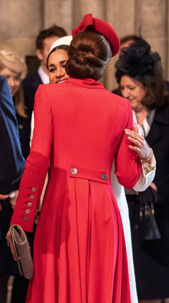 Meghan Markle and Kate Middelton share a kiss on the cheek.