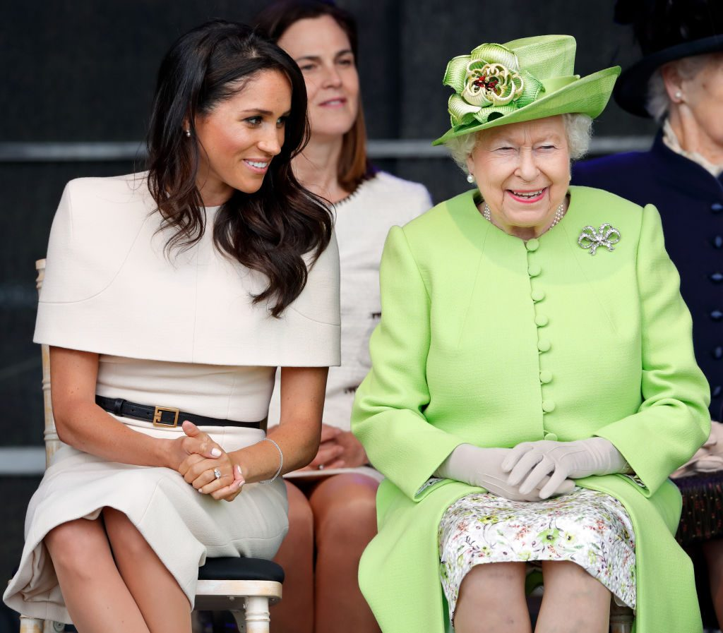 Meghan Markle and the Queen talk during a ceremony.