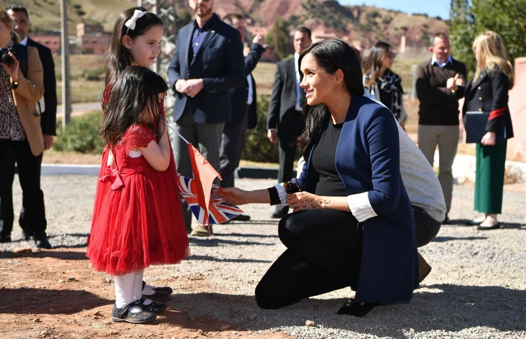 Meghan Markle talks to two girls the henna design on her hand after a visit to the 'Education For All' boarding house in Asni Town, Atlas Mountains on the second day of her tour of Morocco with Prince Harry.