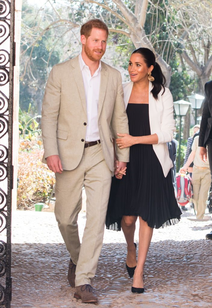 Prince Harry and Meghan Markle hold hands while visiting the Andalusian Gardens in Morocco.
