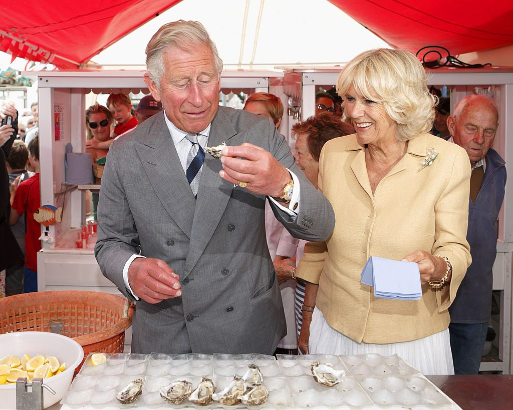 Prince Charles eating oysters with Camilla next to him