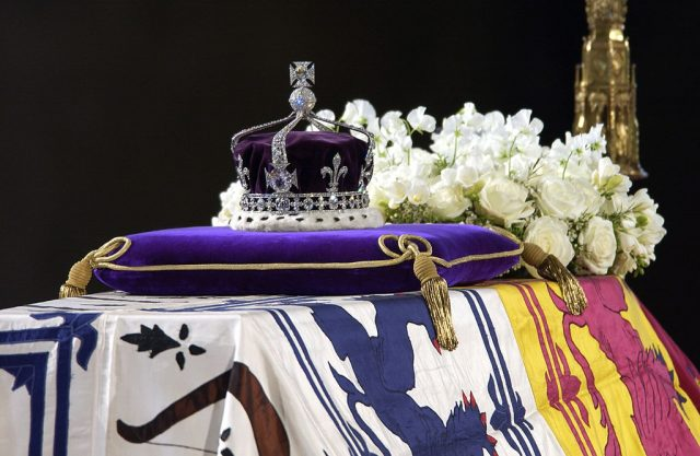 A close up of the coffin with the wreath of white fowers and the queen mother's coronation crown with the Koh-i-Noor diamond.