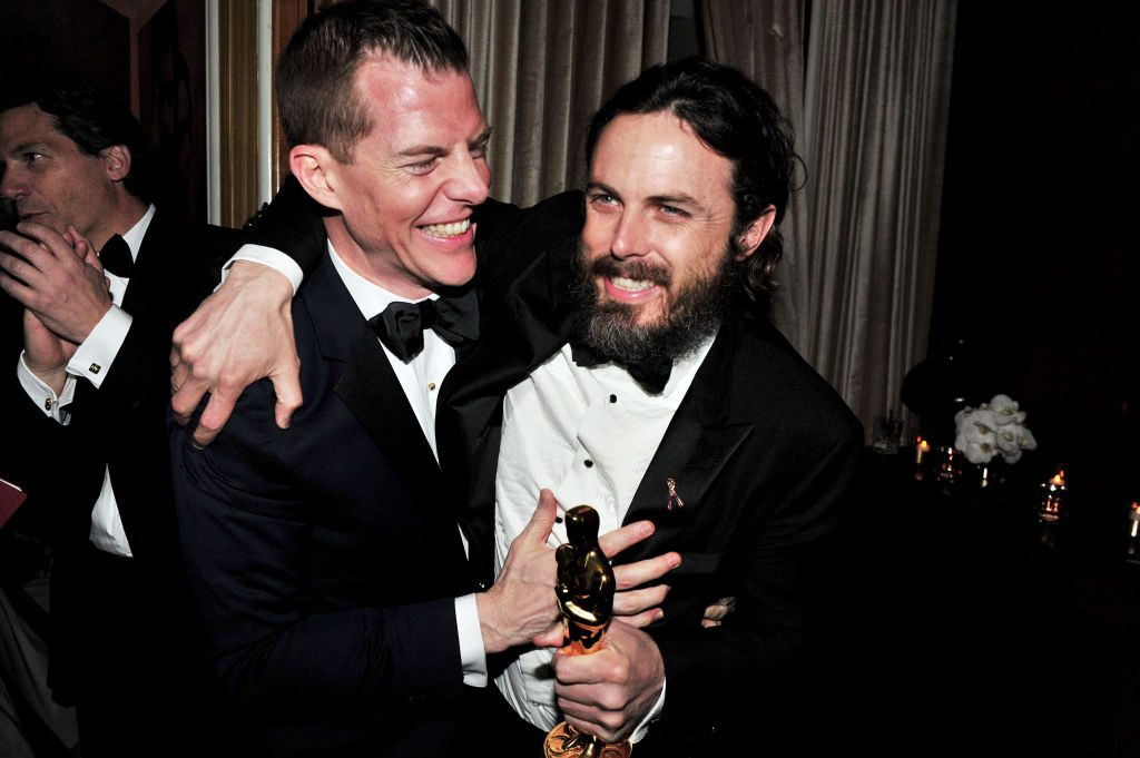 Backstage, Casey Affleck smiles and holds his Oscar award for best actor in 'Manchester By The Sea'
