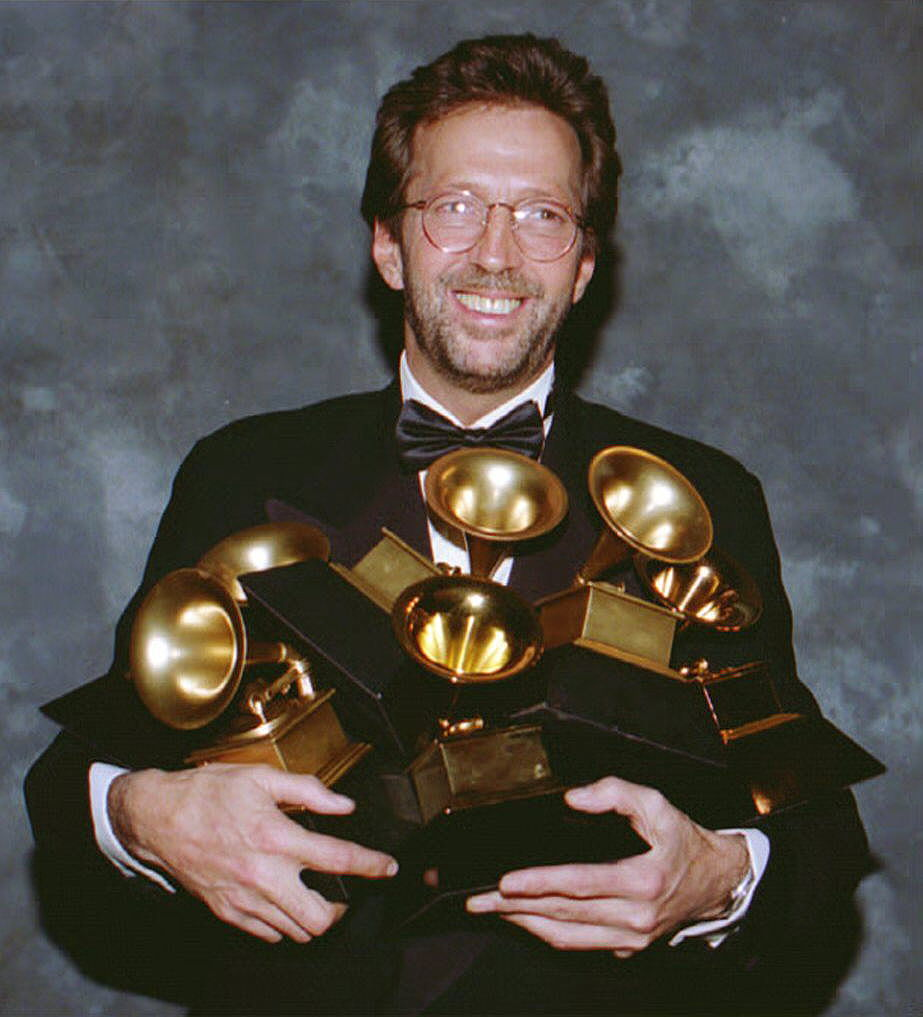 Eric Clapton cradles his six Grammy Awards and poses for a picture