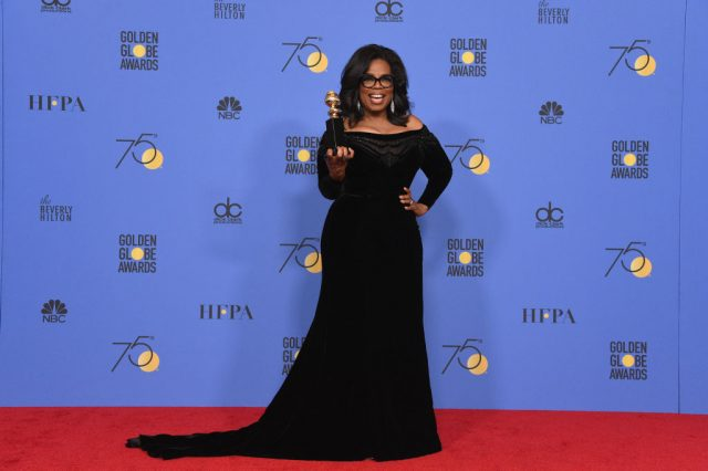 Oprah Winfrey at the Golden Globes holding Cecil B. DeMille award.