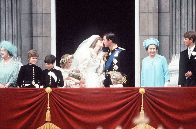 Princess Diana and Prince Charles kissing on balcony of Buckingham Palace after wedding ceremony.