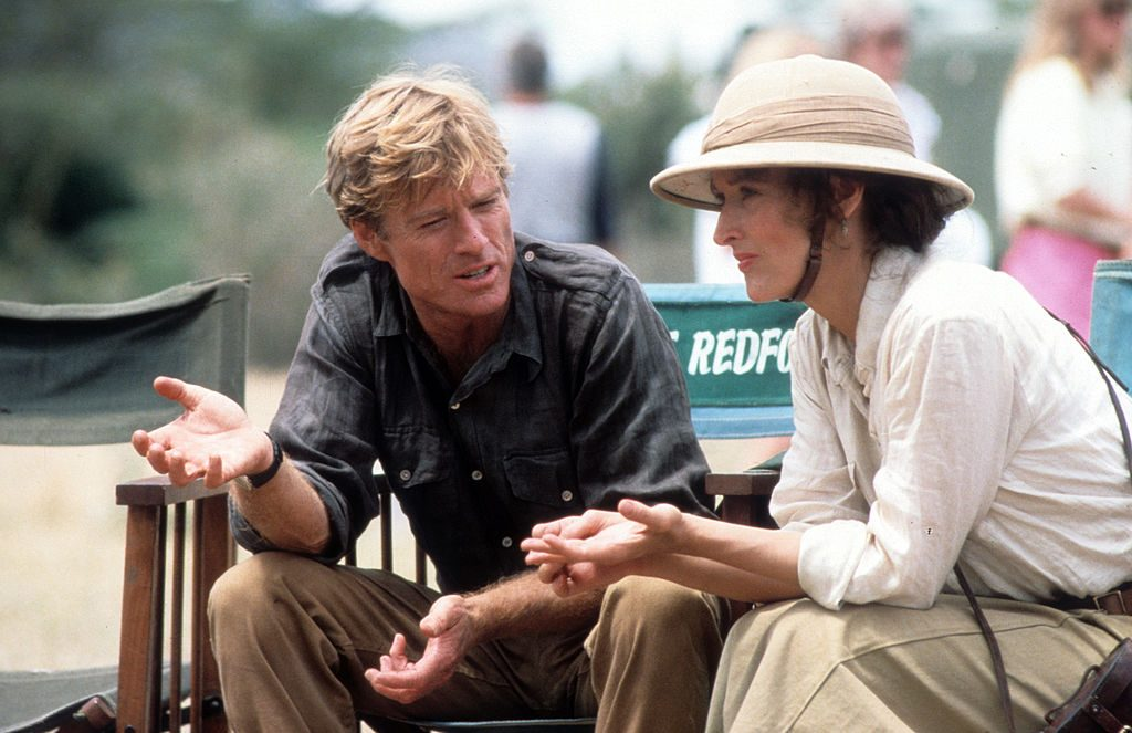Meryl Streep and Robert Redford sit and talk together on the set of Out of Africa.