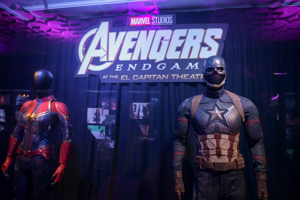 Captain Marvel's and Captain America's suits on display in front of Avengers: Endgame poster