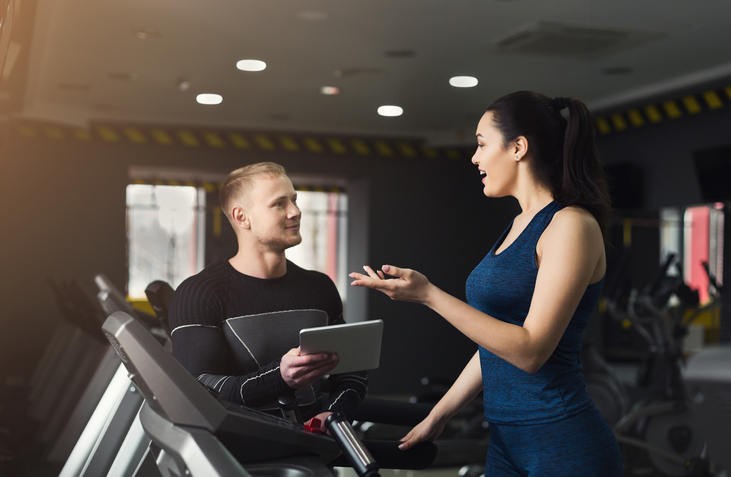 Personal trainer helping girl at gym