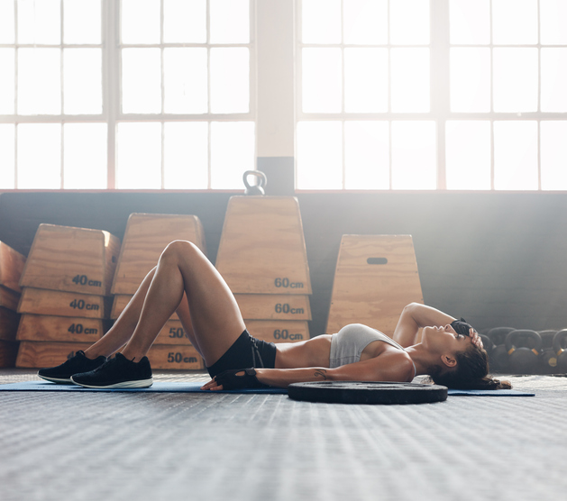Young woman lying on gym floor