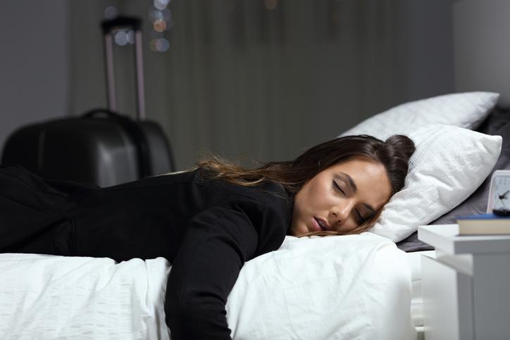Woman asleep on hotel bed