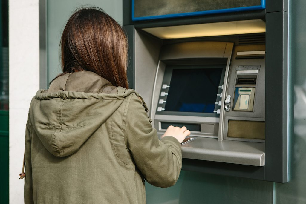 Woman withdraws money from an ATM