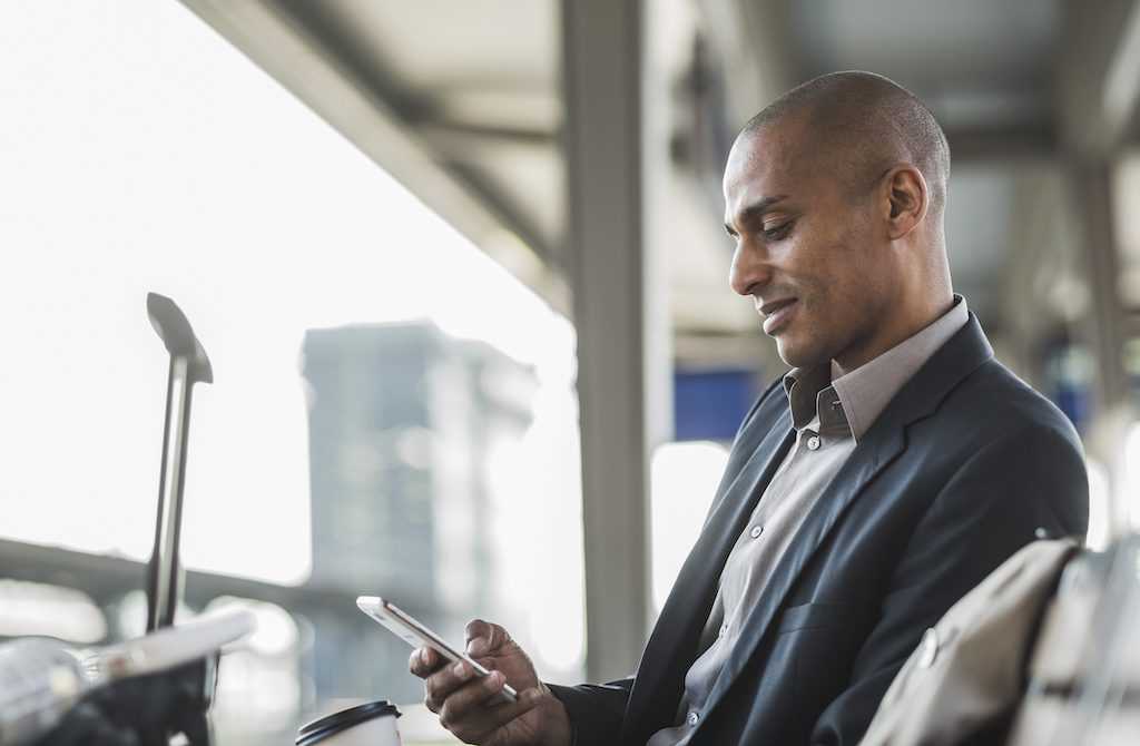 Businessman with phone at airport