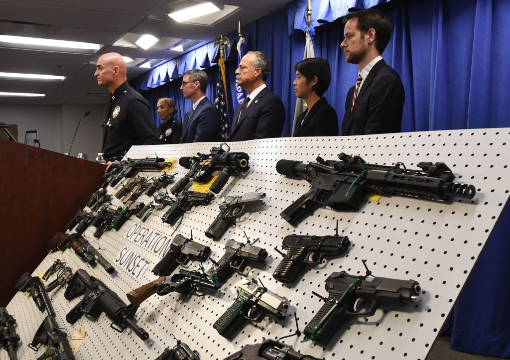 LAPD and FBI representatives display weapons seized after a raid