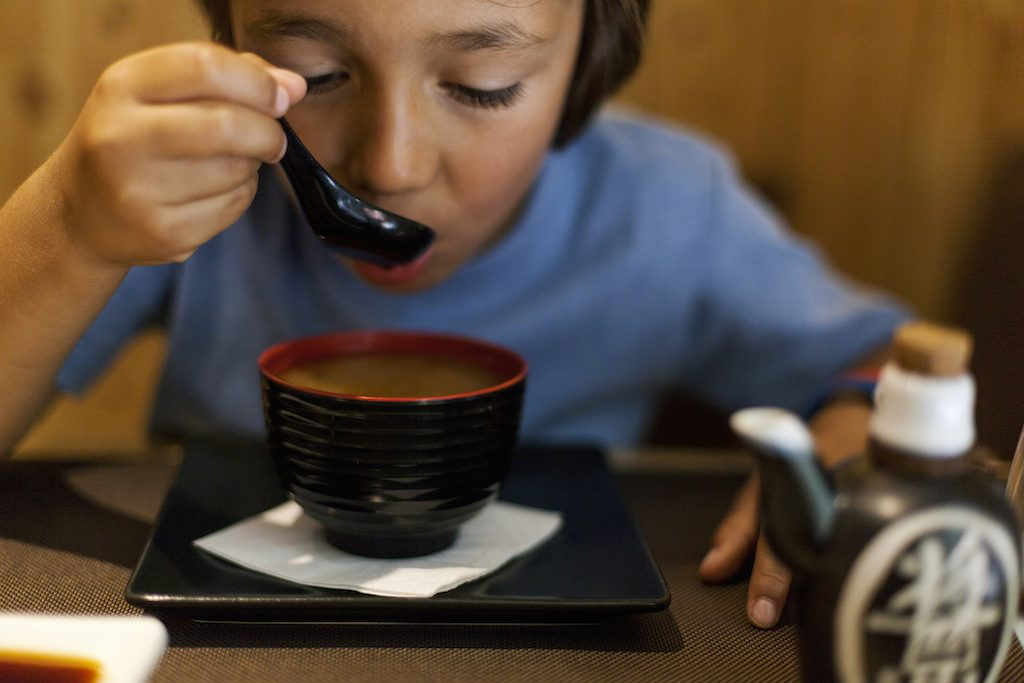 Little boy eating miso soup