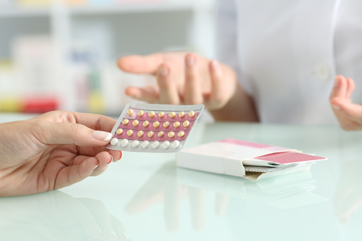 A woman holding birth control pills