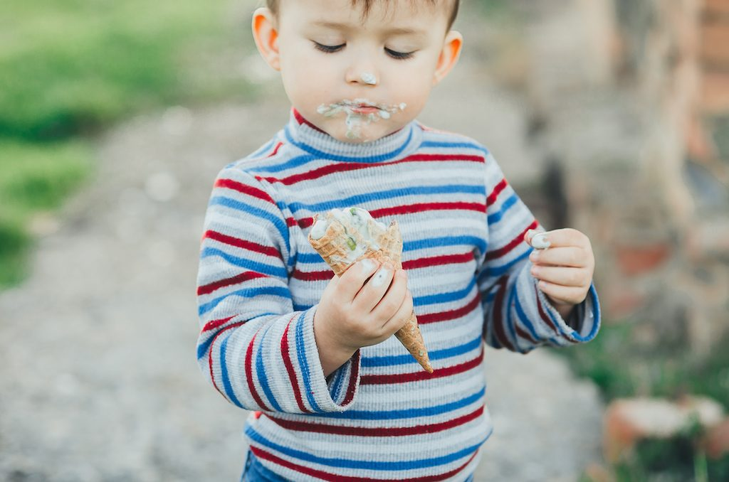 little boy eating ice cream three years very appetizing, amid nature, green grass