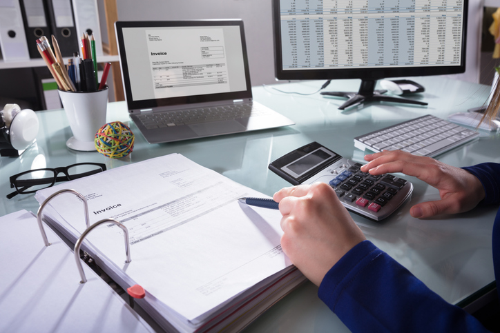 Businessperson checking numbers on a calculator