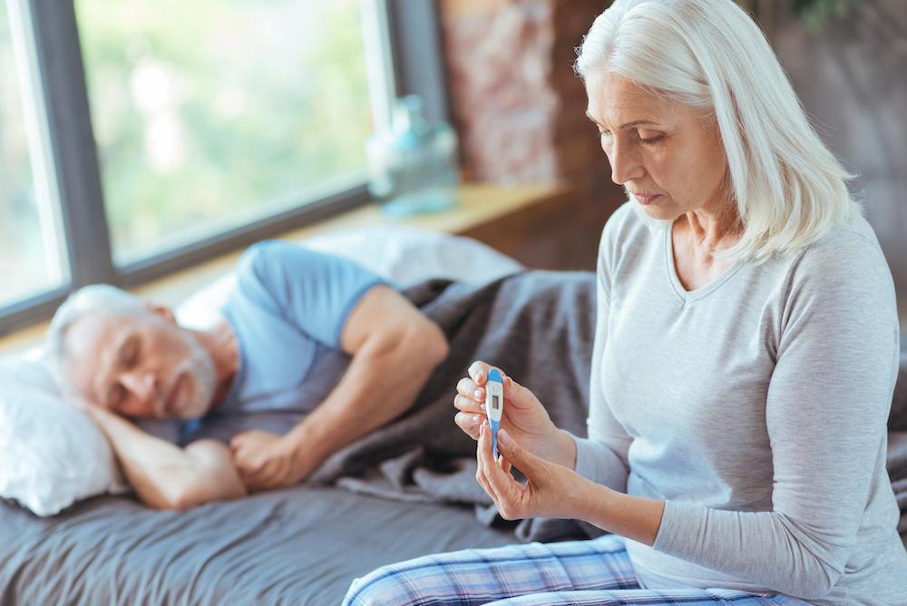 Woman taking a sick man's temperature