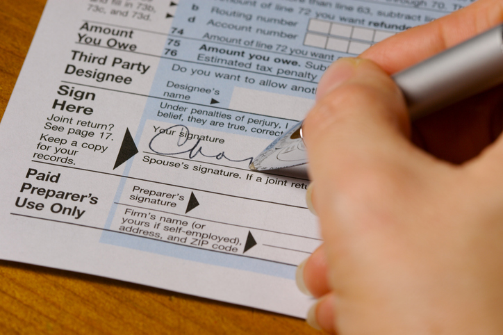Close up of someone signing a tax form