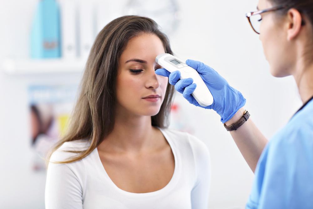 Nurse taking a patient's temperature