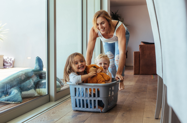Happy woman pushing kids in a laundry basket