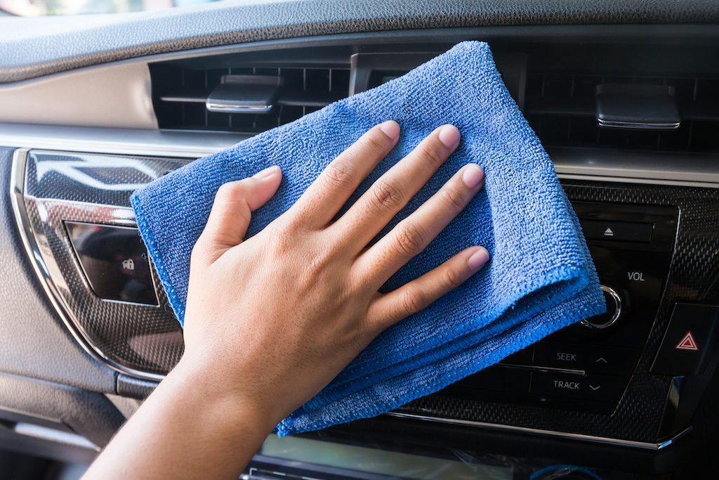 Hand with microfiber cloth cleaning car dashboard
