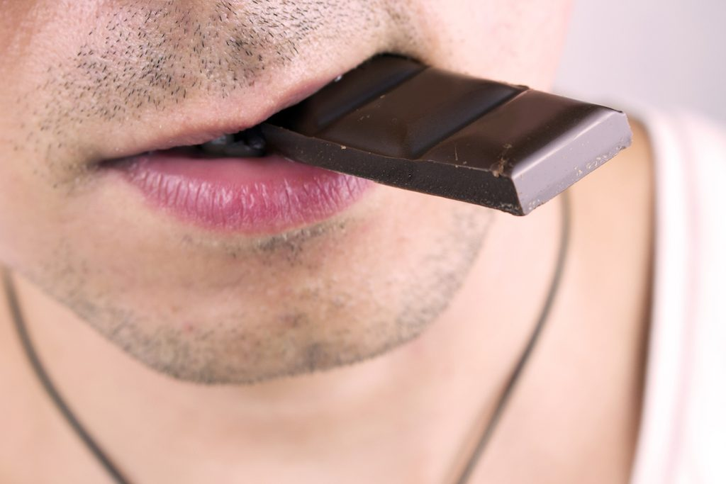 Young man eats dark chocolate