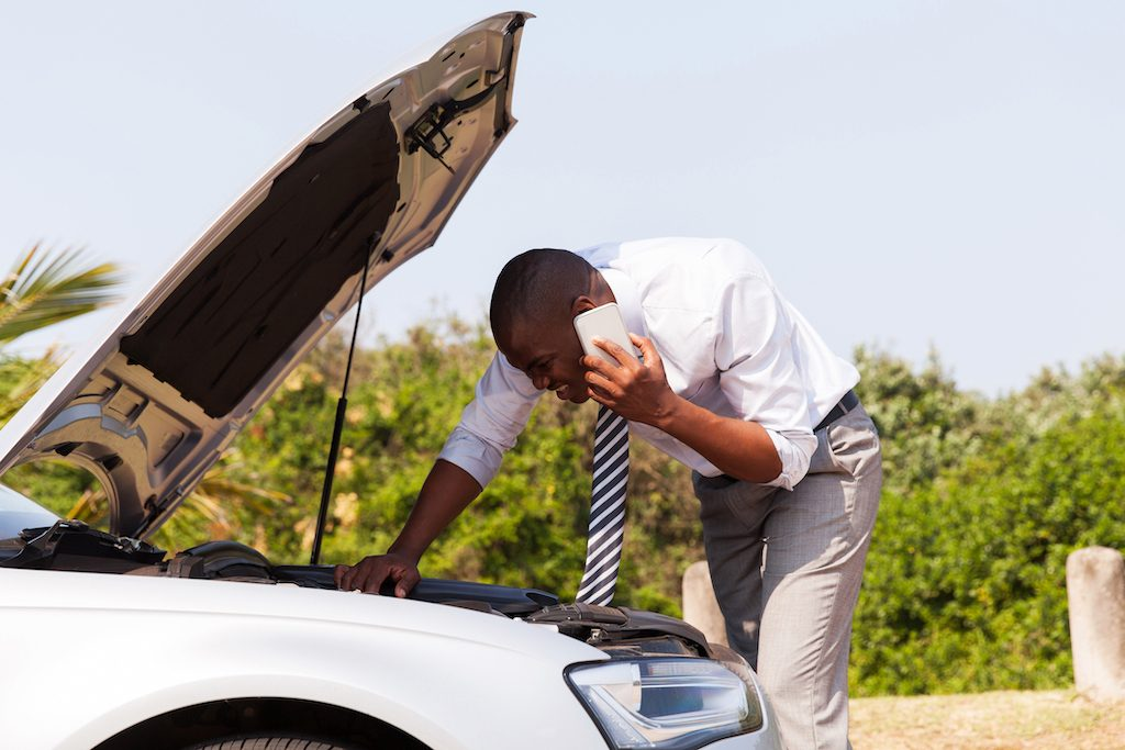 Man checks under hood of broken down car