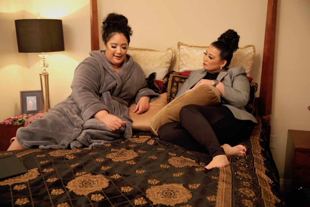 Sunhe and Angelica sit on a bed