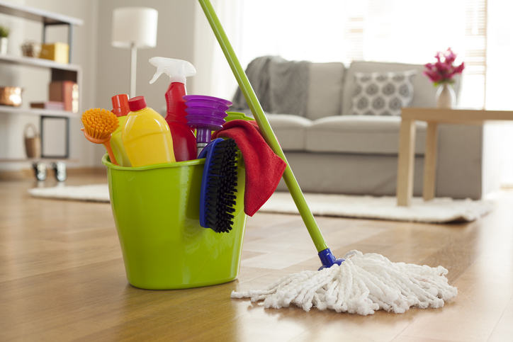 Bucket of cleaners next to a mop