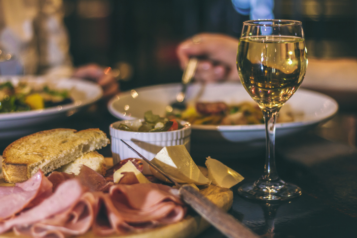 A glass of wine and a restaurant meal