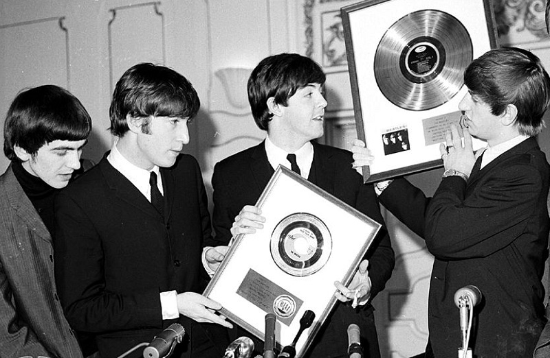 The Beatles celebrate gold records.