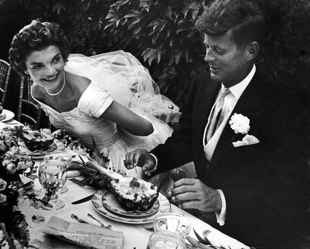 Senator John Kennedy & his bride Jacqueline in their wedding attire, as they sit down together at table to begin eating a pineapple salad at formally set table outdoors at their wedding reception.