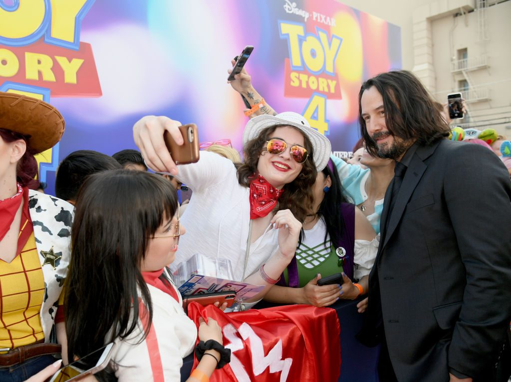 Keanu Reeves takes selfies with fans at the Toy Story 4 premiere