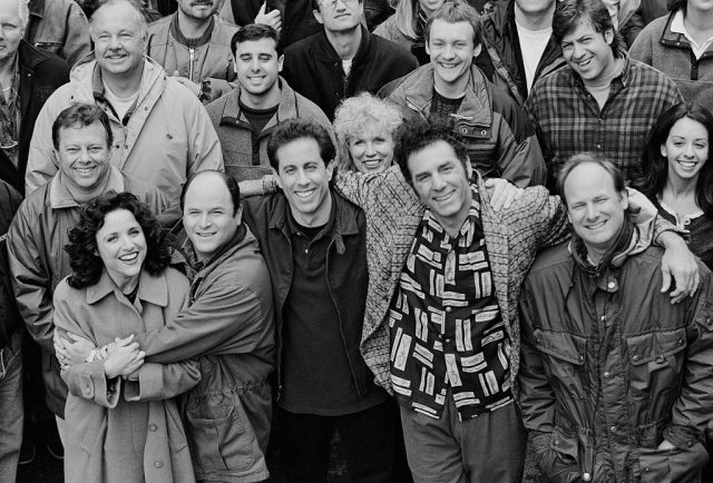 """The cast and crew of the hit television show """"Seinfeld"""" pose on set during the last days of filming the final episode, April 3, 1998 in Studio City, California.. From left to right in the front row are actors Julia Louis-Dreyfus (Elaine), Jason Alexander (George), Jerry Seinfeld (Jerry), Michael Richards (Kramer), and director Andy Ackerman."""