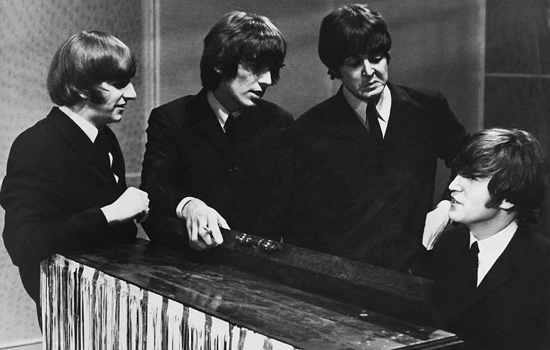 Beatles stand around John Lennon at the piano.